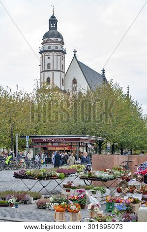 Leipzig, Germany - October 2018: Saint Thomas Church Seen From Plants And Flowers Stalls At Marktpla
