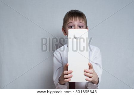 Little Blond Boy Holds And Shows A Big White Carton Package. White Shirt And Red Tie. Light Backgrou