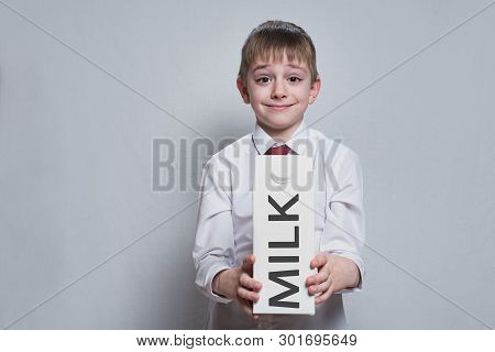 Little Blond Boy Holds And Shows A Big White Carton Milk Package. White Shirt And Red Tie. Light Bac