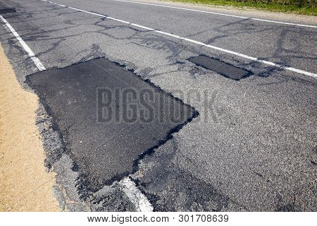 An Asphalt Road On Which Is Repaired And Patches On A Large Number Of Large Holes, Europe