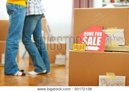 Home For Sale Sign And Hugging Young Couple In Background