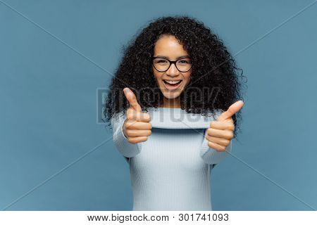 Happy Lovely Woman With Bushy Afro Hair Gives Thumb Up, Approves Nice Idea, Wears Fashionable Sweate