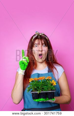 Photo of surprised woman with marigolds pointing hand up