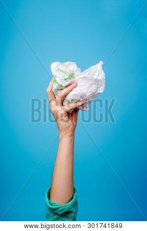 Hand holding plastic bag against blue background.