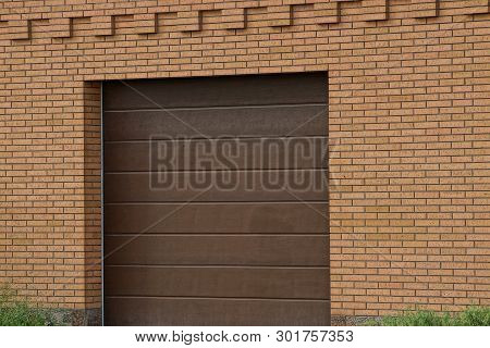Facade Of A Brown Garage With A Closed Gate On A Brick Wall Outside In Green Grass