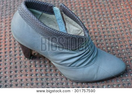 One Gray Leather Shoe With A Heel On A Brown Table