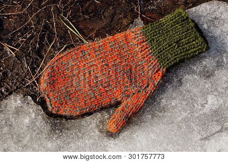 One Colored Wool Mitten Lies On White Snow And Earth