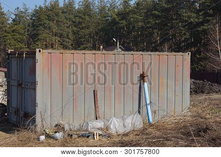 One Brown Metal Container Stands Outside In Dry Grass