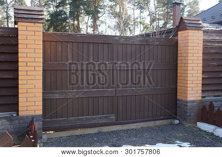 A Large Brown Wooden Plank Gate And Part Of A Brick Fence In The Street