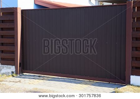 A Large Brown Metal Gate And Part Of A Private Outdoor Fence