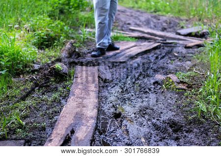 Road Grooves Filled With Water And Mud. Off Road Trails. Man Walk Along The Forest Trail.