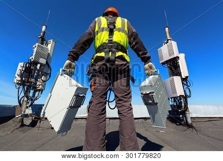 Professional Industrial Climber   In Helmet And Uniform Holds Telecomunication Equipment In His Hand