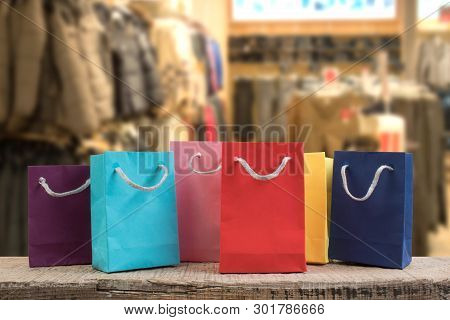 A Lot Of Multi-colored Paper Shopping Bags On A Wooden Table In A Shop. Front View.