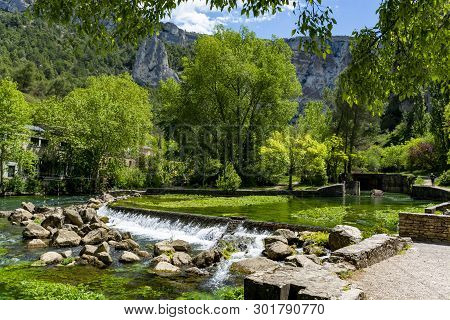 South Of France, View On Small Touristic Provencal Town Of Fontaine-de-vaucluse With Emerald Green W