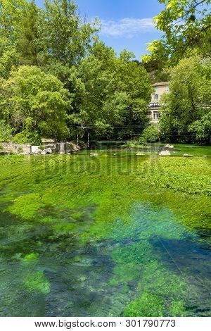 South Of France, View On Small Touristic Provencal Town Fontaine-de-vaucluse With Emerald Green Wate