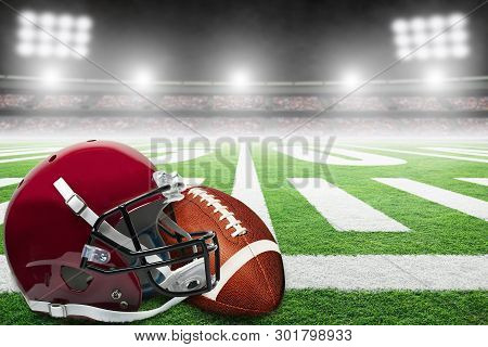 Close Up Of American Football Helmet And Ball On Stadium Field With Yard Line Markings And Spotlight