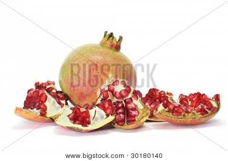 a pomegranate fruit and some pieces with its arils on a white background