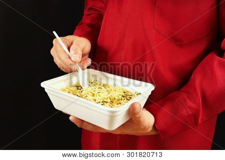 Hands Of Man In A Red Shirt Are Holding A Container With Cheap Instant Noodles On A Black Background