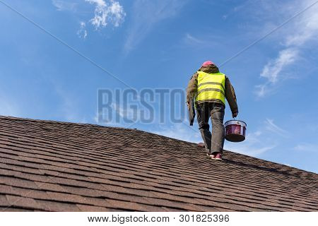 Unrecognizable And Skilled Workman In Uniform Standing On Tile Roof Of New Home Under Construction W