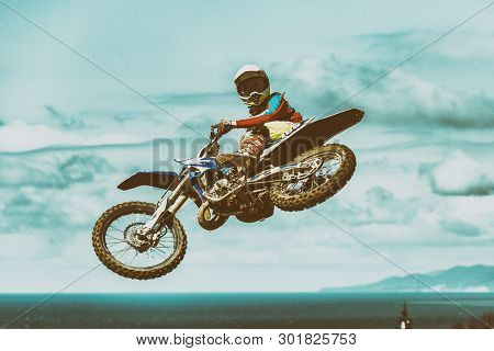 A picture of a biker making a stunt and jumps in the air poster