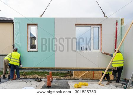 Process Of Construction New And Modern Modular House From Composite Sip Panels. Three Workman In Spe