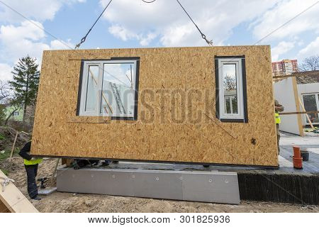 Process of construction new and modern modular house. Workman in special protective uniform wear standing behind sip panel and working on building development industry of energy efficient property poster