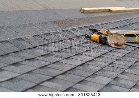 Photo Of Toolbelt With Instrument And Nail Gun Lying On Asphalt Or Bitumen Shingle On Top Of The New