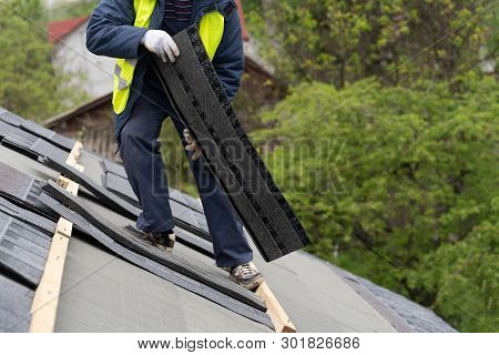 Mature and skilled workman in special protective work wear installing asphalt or bitumen shingle on top of the new roof under construction residential building poster