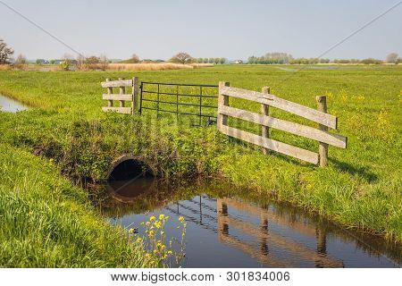 Culvert Under The Access Path To The Meadow. The Wooden And Metal Gate On The Edge Of The Grass Is R