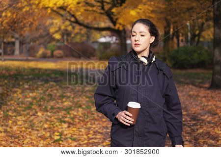 Candid Young Hipster Woman Enjoying Walk Through Park In Autumn Season Holding Coffee To Go Cup In H