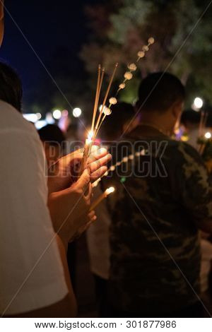Unidentify People With Lighted Candles In Hand During Buddhist Ceremony.