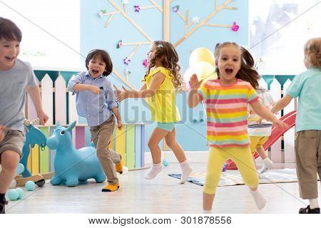 Group Of Happy Children Of Boys And Girls Run In Day Care. Kids Playing In Kindergarten