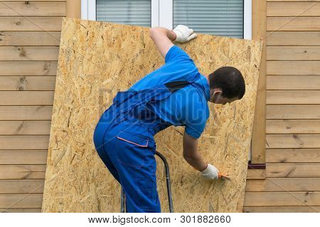 The Owner Of The House Removes The Protection From The Window After A Disaster
