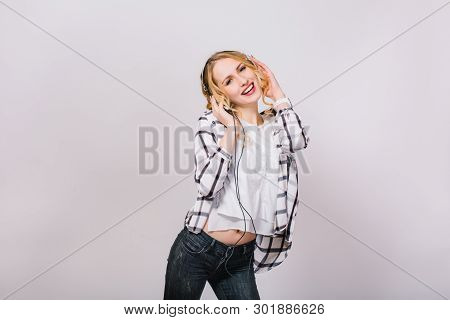 Stylish Photo Of Mirthful Attractive Slim Girl Listening To Favorite Music And Dancing Near Grey Wal