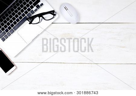 Flat Lay Office Desk Table Of Modern  Workplace With Laptop On White Wooden Table, Top View Laptop B