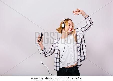Mirthful Gorgeous Girl With Closed Eyes Enjoying Music, Dancing And Holding Smartphone In Hand. Part