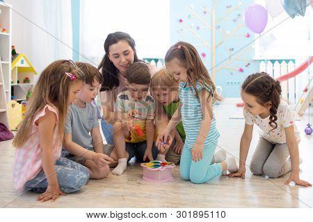 Female Teacher Teaching Kids Play Toy In Classroom. Kindergarten Preschool Concept