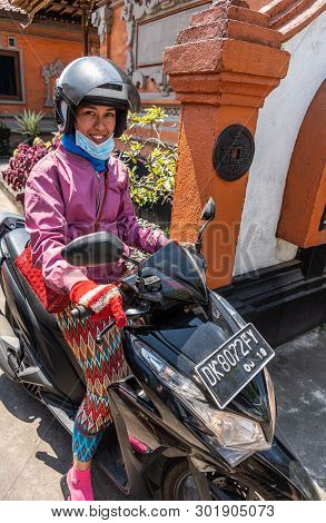 Bali, Indonesia - February 25, 2019: Young Woman With Helmet, Sitting On Black Motorbike Smiles. She