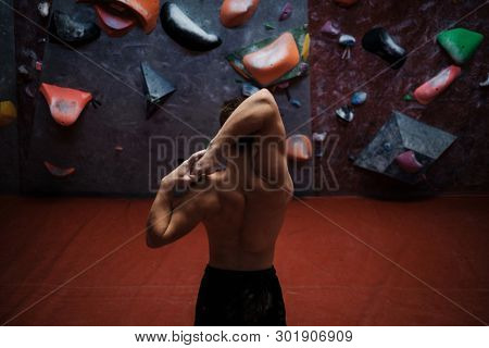 Athletic man stretching before climbing in a bouldering gym