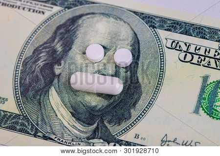 A Pills Lie In Place Of The Eyes, On A Bill Of One Hundred Dollars Close-up. The Concept Of Insuranc