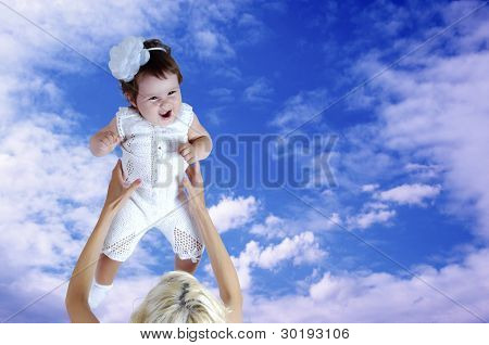 Child in white in mother hands under sky background