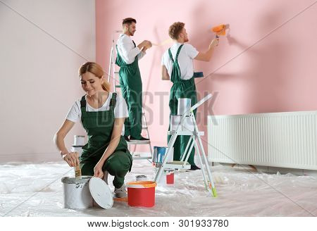 Team Of Professional Decorators Painting Wall Indoors. Home Repair Service