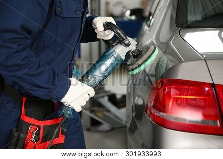 Technician Polishing Car Body With Tool At Automobile Repair Shop, Closeup