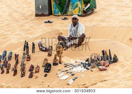 Aswan Egypt 20.05.18 Men Souvenier Seller With Rolling Store On The Bay Sand Near Assuan In Egypt