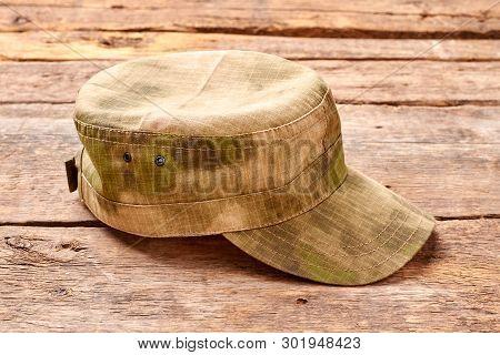 Military cap on wood. Khaki hat on wooden desk. poster