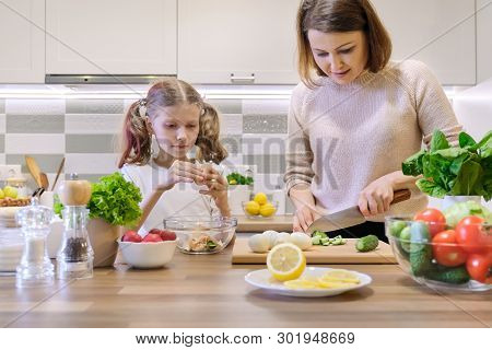 Mother And Child Cooking Together At Home In Kitchen. Healthy Eating, Mother Teaches Daughter To Coo