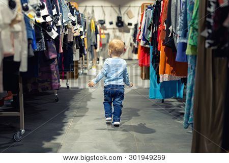 Cute Caucasian Blond Toddler Boy Walking Alone At Clothes Retail Store Between Rack With Hangers. Ba