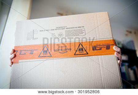 Paris, France - Mar 16, 2019: Hands With Amazon Prime Video Logotype On The Cardboard Box Carton Par