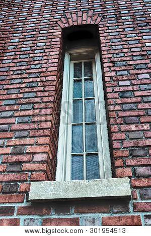 Abstract Brick Wall With Narrow Church Window And Glass
