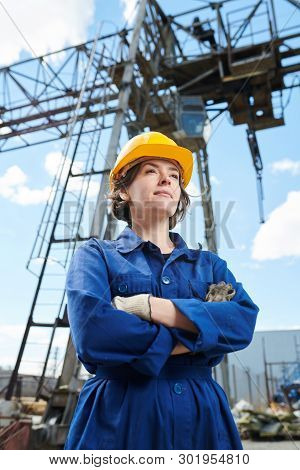 Low Angle Portrait Of Empowered Woman Working At Construction Site Standing Against Tower Crane In B